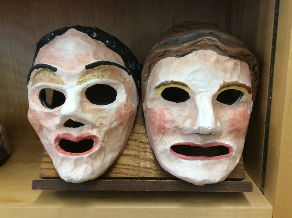 Two paper-maché female face masks from the NEH Roman Comedy Institute. Both have sizable eye holes. One has black hair and a heart-shaped mouth; the other has brown hair and a wide mouth.
