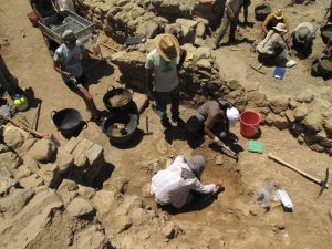 Cicek Beeby (lower right) and Catharine Judson (top right) directing excavation in the Early Iron Age-Orientalizing Building | Photo by Donald Haggis
