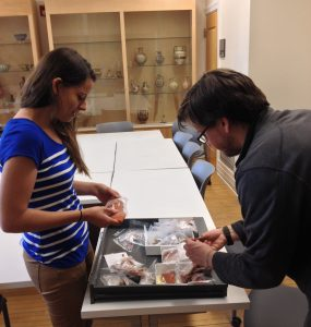 Archaeology graduate students Robyn LeBlanc and Daniel Schindler shift through a tray of pottery samples.