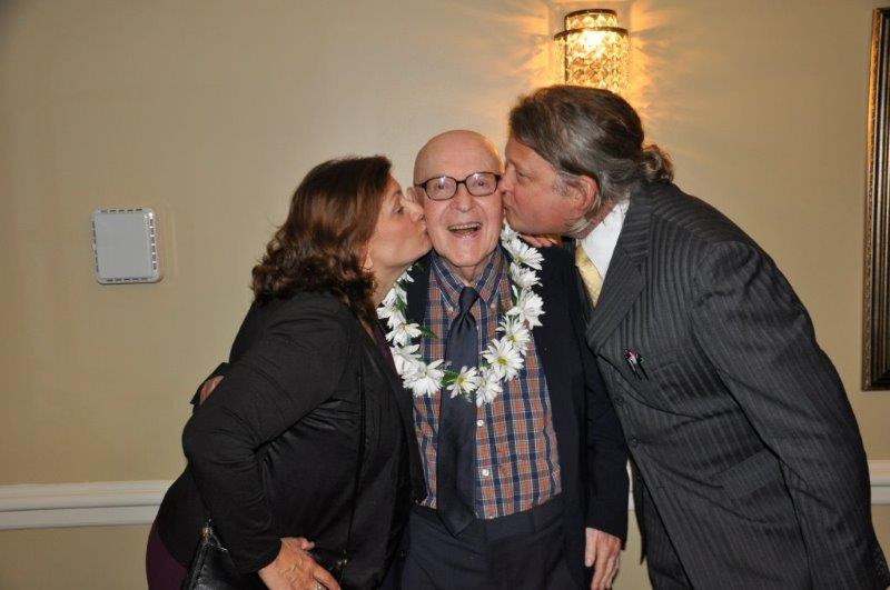 Prof. Linderski enjoys the affections of his former student Hans-Freidrich Mueller and Prof. Mueller's wife, Terri. | Photo by Tina Turner