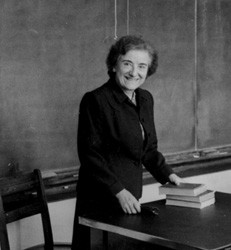 Berthe Marti, smiling, stands in front of a desk with a stack of books.