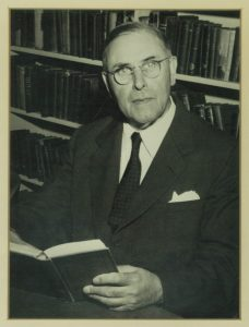 Berthold L. Ullman holds a book in his hands.