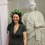 Kelly McArdle in front of Athena/Minerva in Murphey Hall with an ivy wreath on her head.